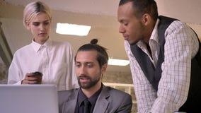 Tres trabajadores multy-étnicos discuten la idea en el ordenador portátil en oficina, concepto coworking, concepto de la comunica almacen de metraje de vídeo