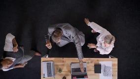 Tres trabajadores multy-étnicos están bailando cerca de la tabla con los ordenadores portátiles en la oficina, concepto del parti almacen de metraje de vídeo