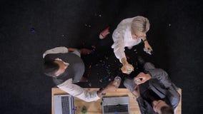 Tres trabajadores multy-étnicos tintinean los vidrios, bebiendo el champán en oficina, las galletas de las grietas de la mujer, c almacen de metraje de vídeo