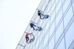 Tres trabajadores que limpian servicio de las ventanas en el alto edificio de la subida imagenes de archivo