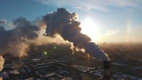 Tres tubos blancos y rojos industriales fuman contra el sol que pone en contraste almacen de metraje de vídeo