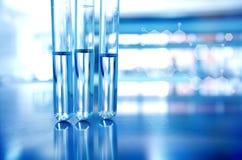 Tres tubos de ensayo con el azul en laboratorio de ciencia de la tecnología con Imágenes de archivo libres de regalías