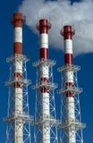 Tres tubos de la fábrica que fuman con humo en fondo del cielo azul Imagen de archivo libre de regalías