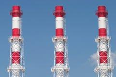 Tres tubos industriales del color en el cielo azul Imagenes de archivo