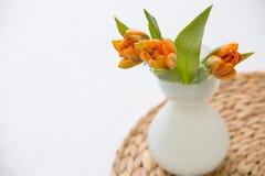 Tres tulipanes anaranjados de la primavera fresca en un florero de cristal blanco agradable en el tablero de paja Decoración case Foto de archivo libre de regalías