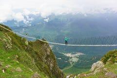 Tres turistas que caminaban en un puente de cuerda estiraron sobre la garganta a la estación de esquí Fotos de archivo