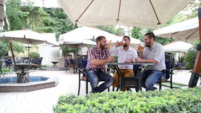 Tres varones en café que beben la cerveza ligera almacen de video