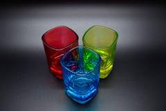 Tres vasos de medida multicolores en fondo negro imagenes de archivo