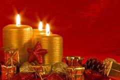 Tres velas ardientes en una configuración de la Navidad Fotos de archivo libres de regalías