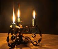 Tres velas ardientes en una palmatoria Fotografía de archivo