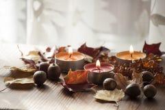 Tres velas ardientes, hojas de otoño coloridas y bellotas del roble rojo septentrional y del collar ambarino Imagenes de archivo