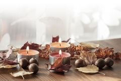 Tres velas ardientes, hojas de otoño coloridas y bellotas del roble rojo septentrional y del collar ambarino Fotos de archivo