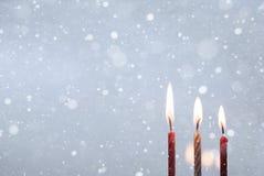 Tres velas ardientes, nieve, fondo azul Imagen de archivo libre de regalías