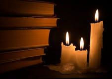 Tres velas blancas del Lit y libros viejos Fotografía de archivo