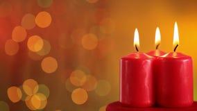Tres velas de la Navidad que queman contra fondo borroso metrajes