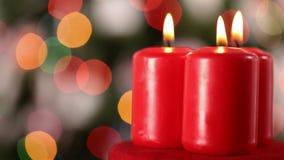 Tres velas de Navidad que hacen girar delante del árbol de navidad borroso almacen de video