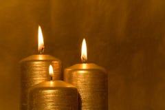 Tres velas de oro de quema imagenes de archivo