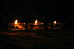 Tres velas decorativas en fondo oscuro Imágenes de archivo libres de regalías