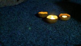 Tres velas en palmatorias de la arcilla están en la oscuridad en la pila de la alfombra con un azul marino grande almacen de metraje de vídeo