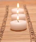 Tres velas en una alfombra de bambú Fotografía de archivo