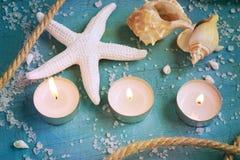 Tres velas, estrellas de mar y cáscaras ardientes en el vint de la turquesa Fotografía de archivo libre de regalías