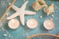 Tres velas, estrellas de mar y cáscaras ardientes en la turquesa detrás Foto de archivo