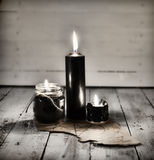 Tres velas negras y manuscrito viejo con pentagram en la tabla de madera Fotos de archivo libres de regalías