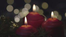 Tres velas rojas de la Navidad están quemando en un fondo borroso de las luces del centelleo almacen de video