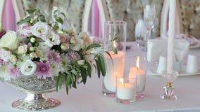 Tres velas y ramos de iluminación de rosas en la tabla de la boda almacen de video