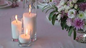 Tres velas y ramos de iluminación de rosas en la tabla de la boda metrajes