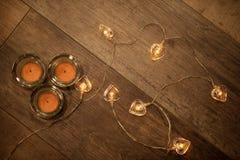 Tres velas y secuencia decorativa en forma de corazón de las luces eléctricas en piso de madera laminado imagenes de archivo
