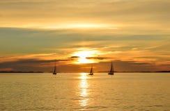 Tres veleros en la puesta del sol Fotografía de archivo libre de regalías