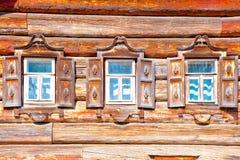 Tres ventanas con la casa de madera del estilo ruso Imágenes de archivo libres de regalías