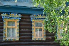Tres ventanas con los platbands tallados detrás de ramas del abedul Imagen de archivo