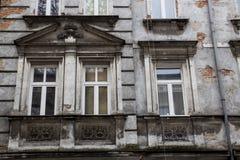 Tres ventanas de diseño del vintage en la fachada del hou viejo desigual Foto de archivo libre de regalías