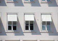 Tres ventanas en el edificio gris con los toldos y la sombra blancos Foto de archivo