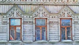 Tres ventanas en la pared de una casa de madera en el estilo ruso Imagen de archivo libre de regalías
