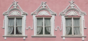 Tres ventanas en la pared rosada de la casa con el estuco adornado Fotografía de archivo libre de regalías