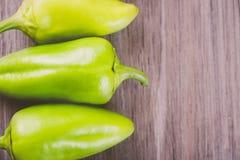 Tres verdes y pimientas amarillas en fila Fotografía de archivo libre de regalías