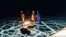Tres viajeros por la derecha del fuego en el hielo en la noche Hielo del camping La tienda se coloca al lado del fuego La gente e almacen de metraje de vídeo