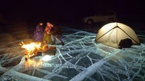 Tres viajeros por la derecha del fuego en el hielo en la noche Camping en el hielo La tienda se coloca al lado del fuego Lago Bai almacen de metraje de vídeo