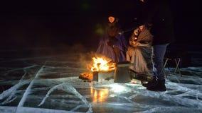 Tres viajeros por la derecha del fuego en el hielo en la noche Camping en el hielo La tienda se coloca al lado del fuego Lago Bai metrajes