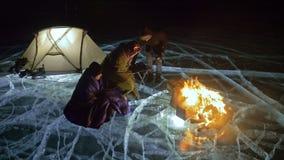 Tres viajeros por la derecha del fuego en el hielo en la noche Camping en el hielo La tienda se coloca al lado del fuego Lago Bai almacen de video