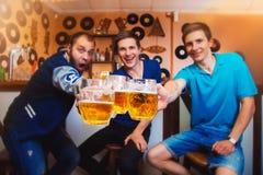 Tres vidrios alegres del tintineo del hombre de cerveza en una barra Foto de archivo libre de regalías