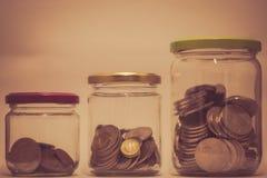 Tres vidrios con el aumento de monedas como piggybank imagenes de archivo