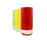 Tres vidrios con el jugo coloreado imagen de archivo