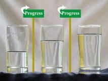 Tres vidrios de agua con concepto del progreso imágenes de archivo libres de regalías