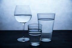Tres vidrios de agua en blanco y azul Fotografía de archivo libre de regalías