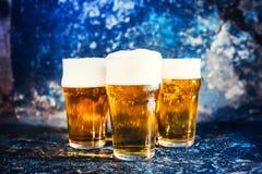 Tres vidrios de cerveza de cerveza dorada, las cervezas ligeras sirvieron frío en el pub Imagen de archivo