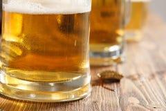 Tres vidrios de cerveza fría en el escritorio de la barra o del pub Fotografía de archivo